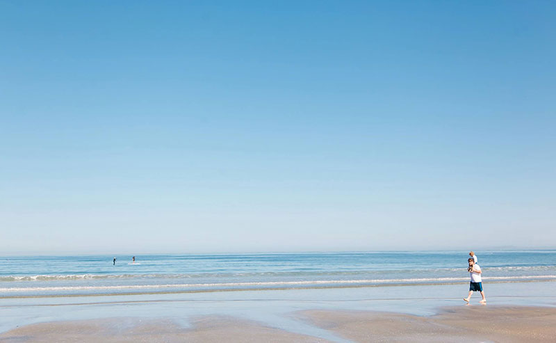 A man with a child on his shoulders walks along the La Jolla Shore with bright blue ocean in the background