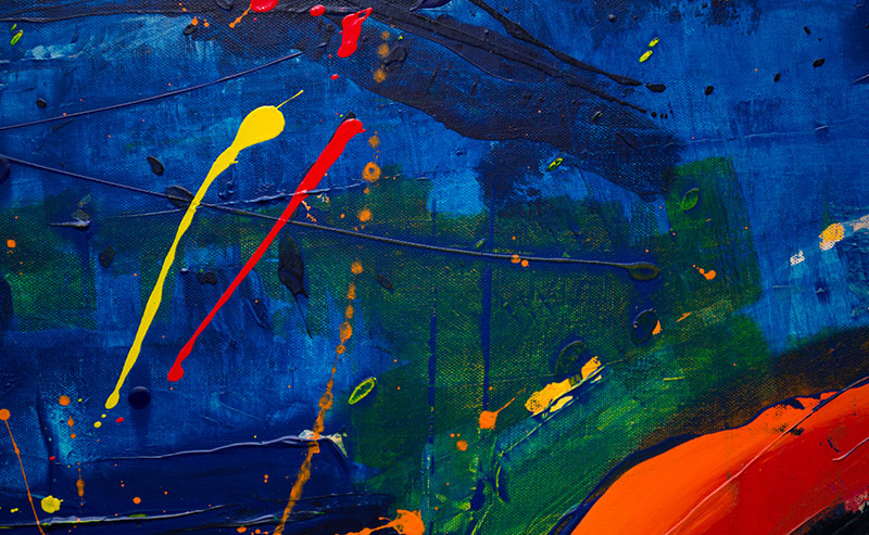 An abstract painting of a blue background with yello, red, and green brush strucks and drippings.