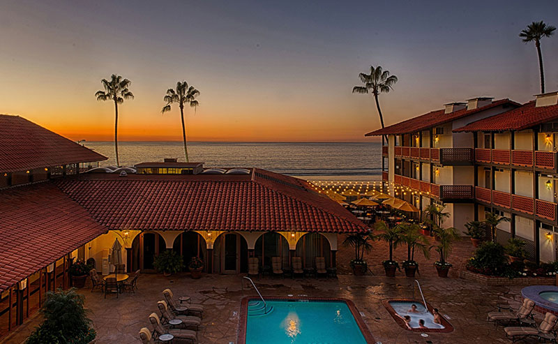 A view of the pool area and outside courtyard of the La Jolla Shores Hotel with the balconies of the hotel rooms surrounding them with palm trees, the ocean, and a pink sunset sky in the background