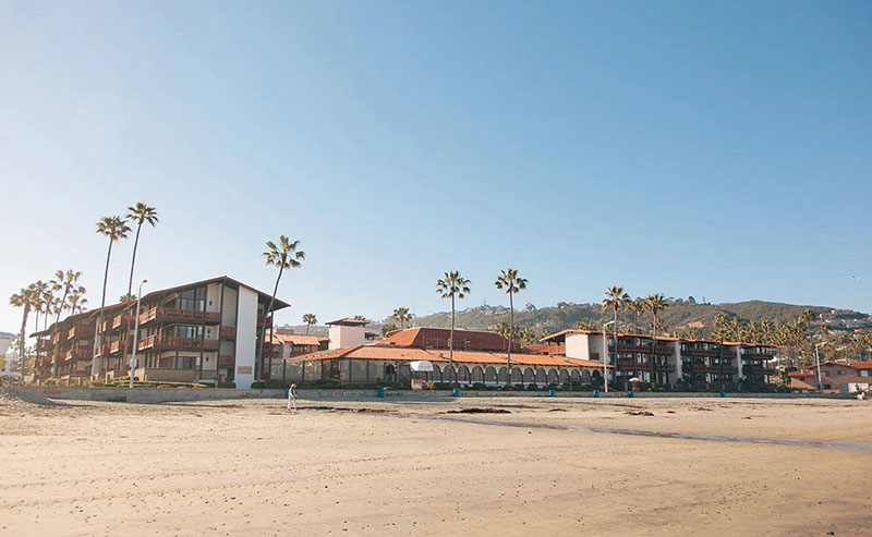 View from the beach of the entire La Jolla Shores Hotel with the sandy beach in the foreground.