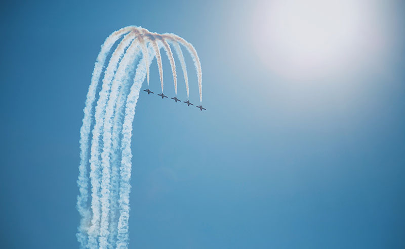 Five Blue Angel jets fly in formation, making a loop and leaving a trail of white smoke behind them.