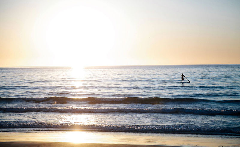 A view of a paddleboarder far out in a calm ocean as the sun sets behind him and reflects off the water
