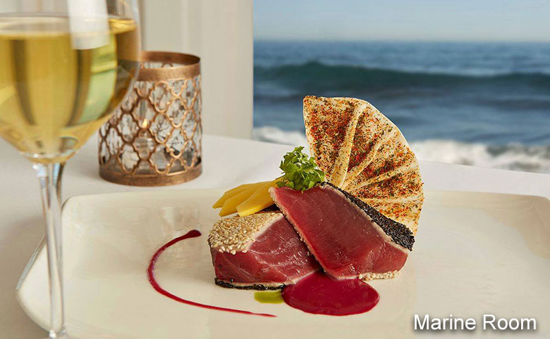 Seared tuna decoratively presented on a white plate with a glass of white wine and a view of the ocean through the window behind the table.