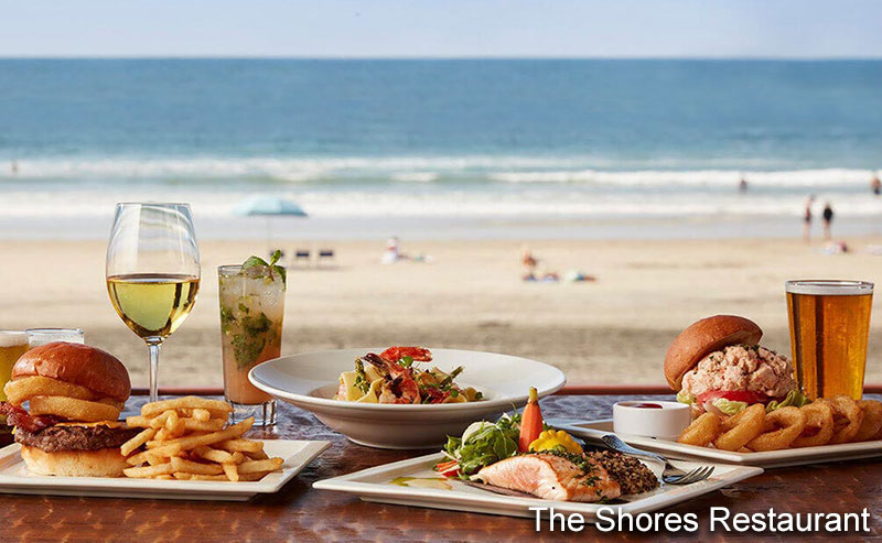 Plates of entrees from the Shore Restaurant, including shrimp cocktail, a hamburger and fries, and grilled fish, surrounded by beverage options of wine and beer and a mixed cocktail, all in front of a window onto the beach and ocean right outside