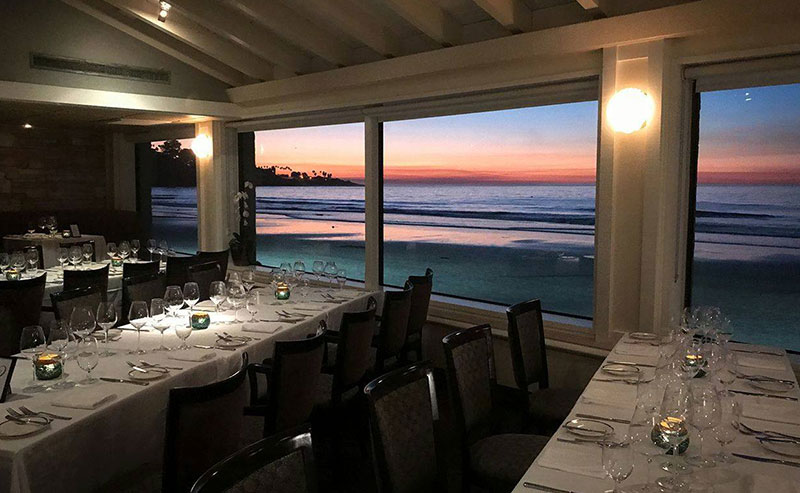 Tables set for the evening next to a window that looks out to sunset over the ocean