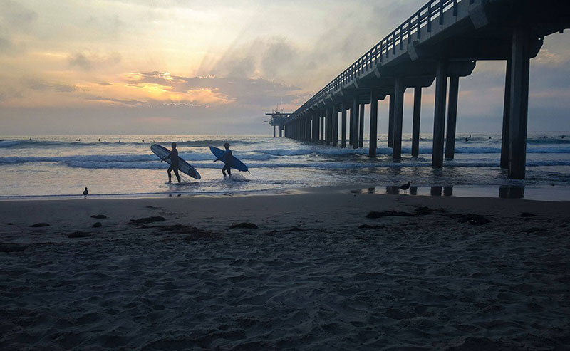2 surfers hold their surfboards as they walk out of the ocean with the La Jolla pier to their right and the La Jolla Shores beach in front of them.