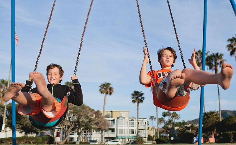 Two kids swing on a swingset in the La Jolla Shores Village