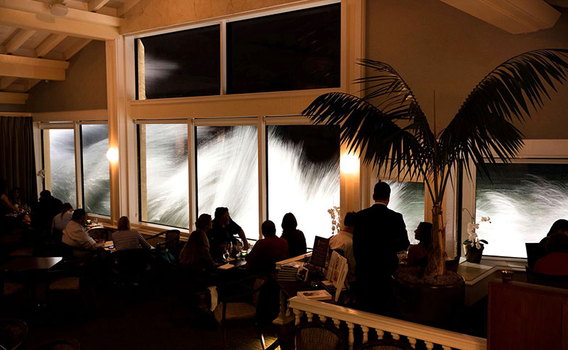 A crowd of diners fill the tables of the Marine Room with a view of the surf crashing from the windows