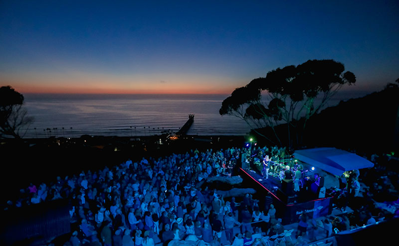 A nighttime view of the crowd at a Green Flash concert, watching the band play, as the last of the sun dissapears behind the ocean