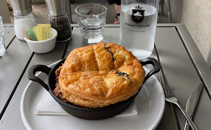 A table at Sugar & Scribe with their Shephard's Pie in a cast iron skillet with a fork and knife crossed next to it