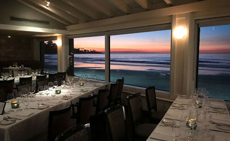 Empty tables set up for dinner with a view out the window onto the setting sun over the waves