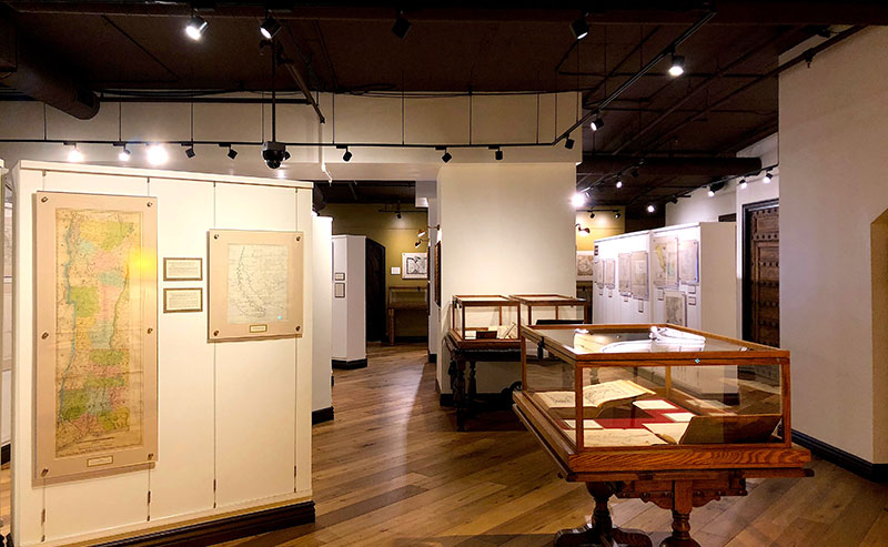 Glass display cases filled with old atlases in front of old maps hung on all the walls