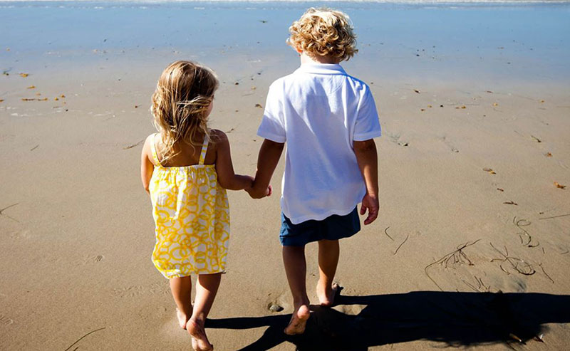 Kids in summer clothes standing on the beach outside La Jolla Shores Hotel, looking at the ocean