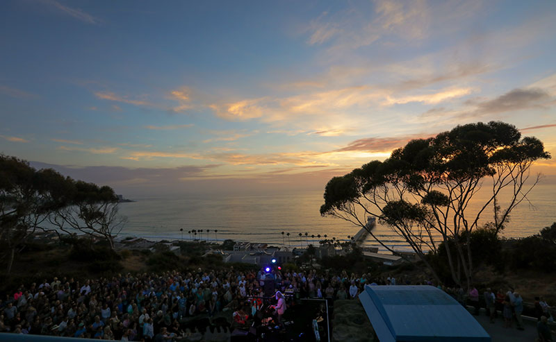 The view from above of the crowd at a Green Flash concert with the ocean and the sun setting in the background