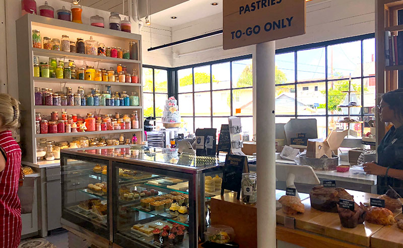 The view inside Sugar & Scribe Bakery of the display case and counter full of pastries, a wall of candy decorations, and the register with a bakery employee