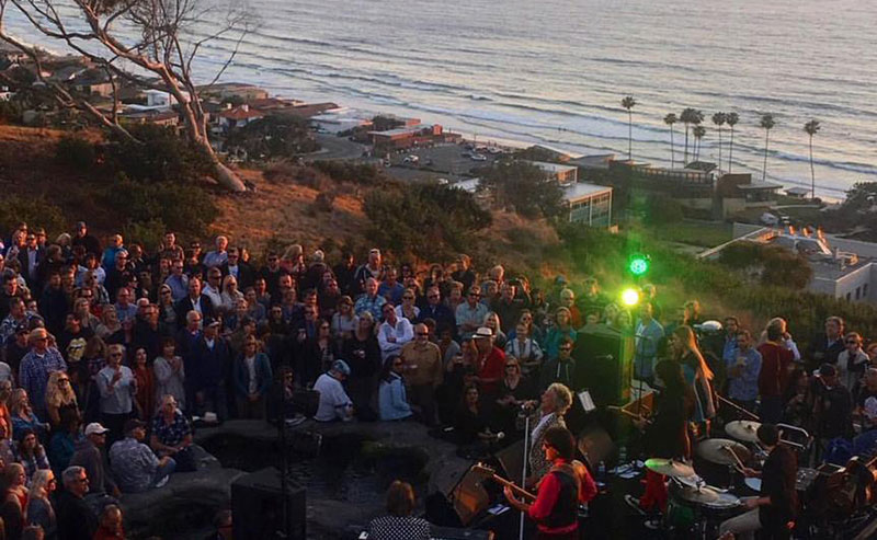 View from behind the band at a Green Flash Concert, looking out on the audience and the ocean and coastline behind them