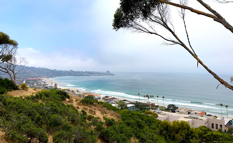 View from the hills above La Jolla Shores reveal the La Jolla Shores Hotel and waves crashing on the beach up and down the coastline
