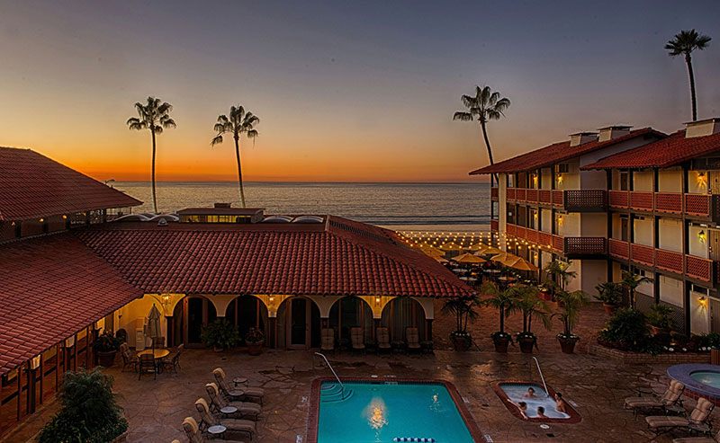 View of the pool area and courtyard of the La Jolla Shores Hotel with the setting sun, ocean, and palm trees in the background