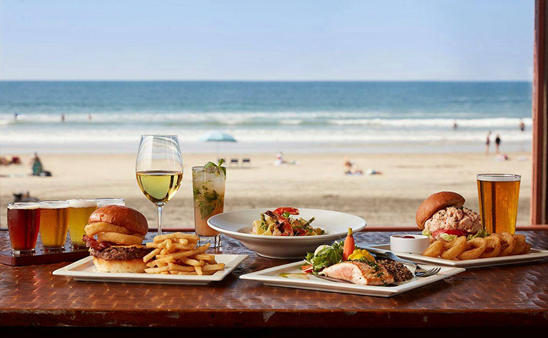 Food and drinks displayed on a table by the window that is facing the beach and ocean at the La Jolla Shores Restaurant. A wide variety of food such as hamburger and fries, grilled fish, and a plate of shrimps. Beverages such as wine, beer, and mixed cocktails.