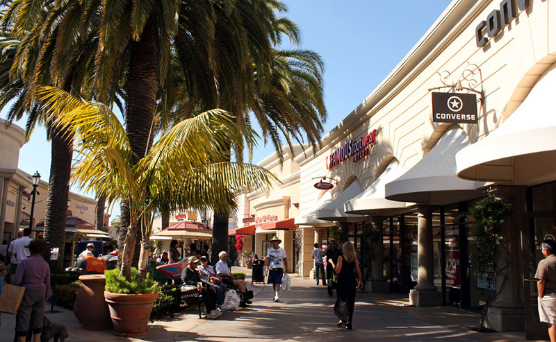 Some shoppers walking and some sitting down, taking a break on benches at Carlsbad Premium Outlets in San Diego.