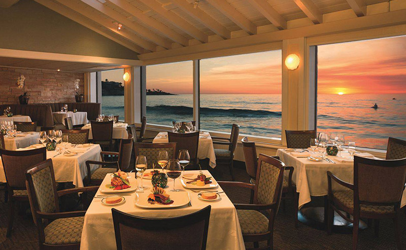 Tables and chairs set for the night next to a window that looks out to the sunset at the Marine Room.