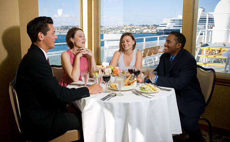 Table that is filled with food, drinks, and serving ware located by the corner of a boat on the glimmering San Diego Bay with an ocean view.
