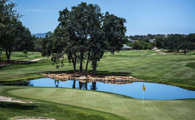A golf course surrounded with trees and a lake in San Diego.