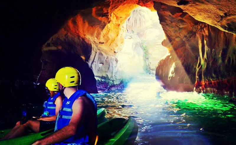 Two kayakers wearing a safety helmet and lifejacket on a green kayak, each exploring the stunning La Jolla sea caves.