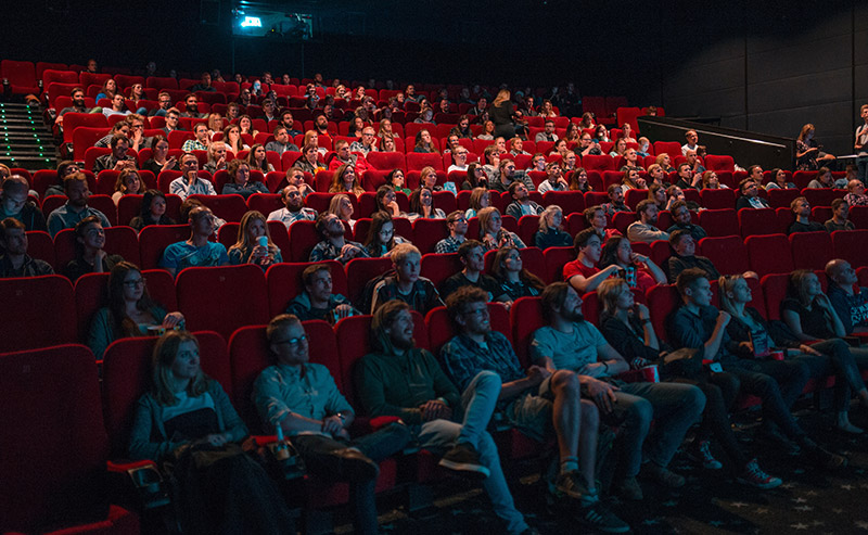 Families seated on red seats watching a movie in a theatre.