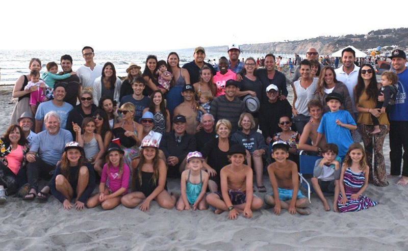 Family members posing for a picture on the sandy beach with the ocean in the background at La Jolla Shores Hotel.