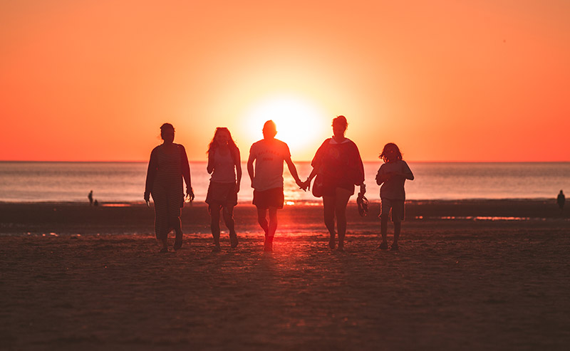 Family members on the La Jolla Shores beach facing the ocean walking towards the sunset.