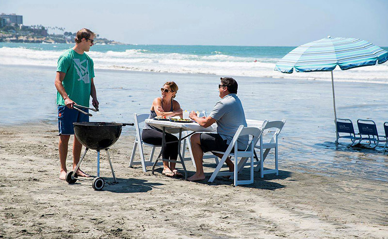 Family having a BBQ cookout on the beach, facing the ocean with a table, chairs, linens, serving ware, and Weber grill provided by La Jolla Shores Hotel.