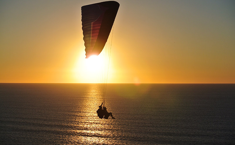 Two people paragliding over the sparkling Pacific ocean during sunset at Torrey Pines Gliderport.
