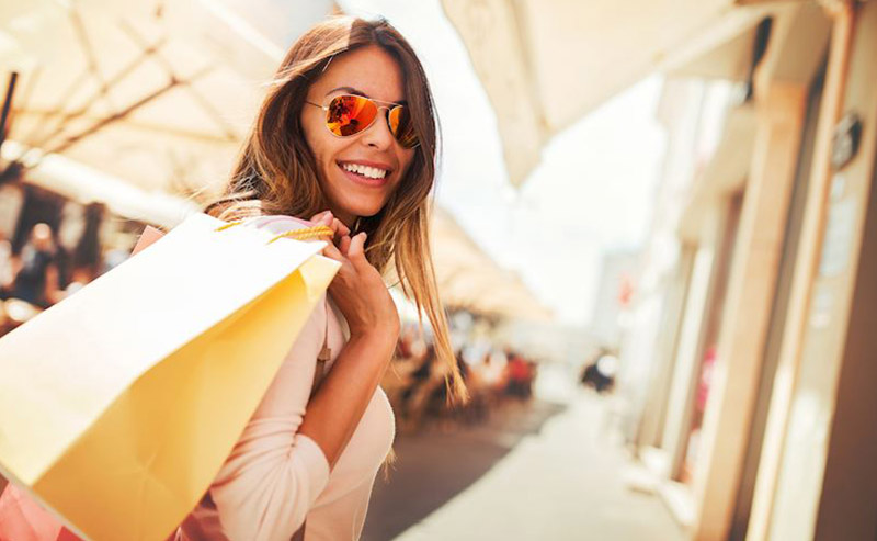 A lady with sunglasses and a wide smile on her face carrying her shopping bags at the outdoor shopping center, Westfield UTC.