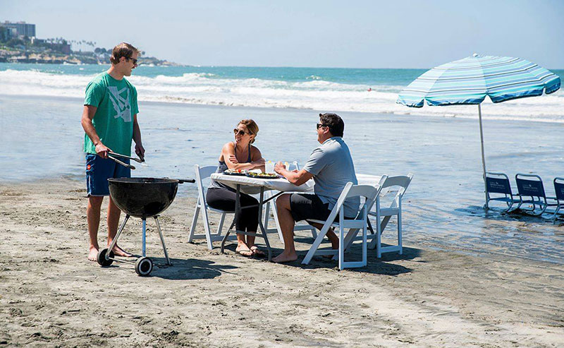 A family enjoying a beach bbq cookout courtesy of La Jolla Shores Hotel