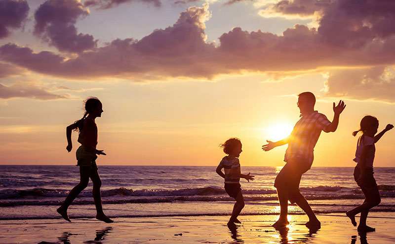 A family of four playing on the beach as the sun sets