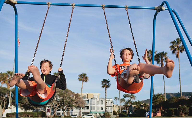Two kids swinging on the swing set at Kellogg Park nearby La Jolla Shores Hotel
