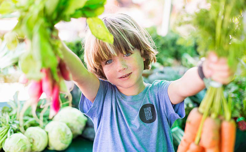 A boy holding up fresh produce at the La Jolla Open Aire Market