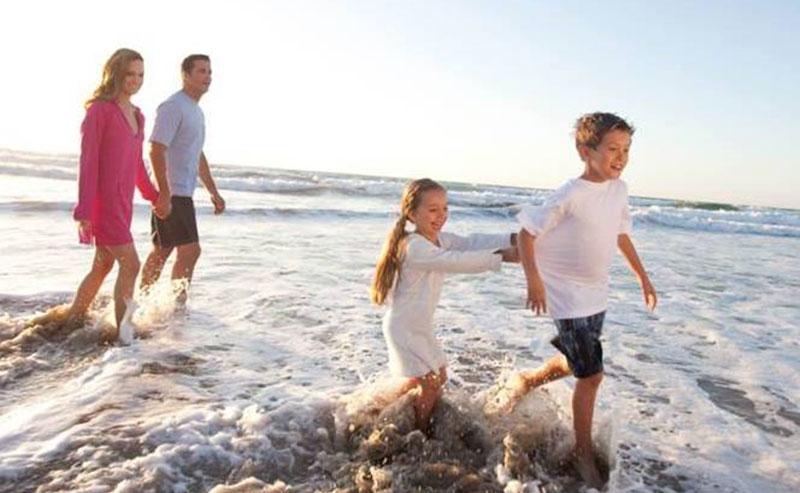 A family of four running through the ocean water along the shoreline at La Jolla Shores beach