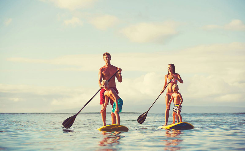 A family of four stand up paddle boarding at La Jolla Shores