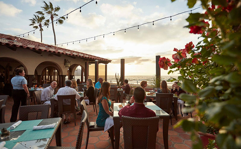 People enjoying happy hour at the La Jolla Shores Restaurant on the patio during golden hour