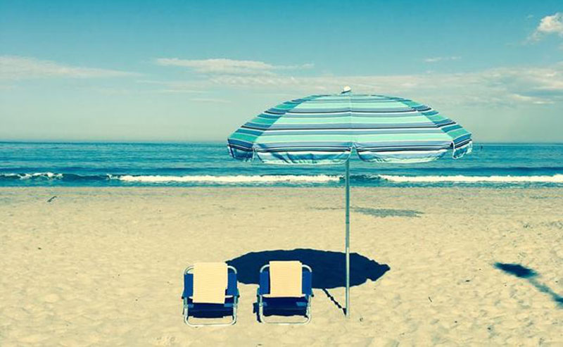 Two beach chairs and an umbrella set up on the beach