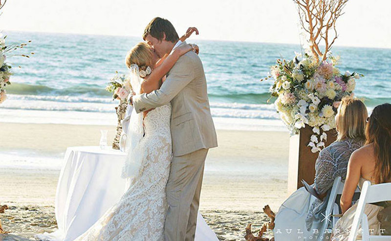 A couple kissing at their beach wedding at La Jolla Shores Hotel