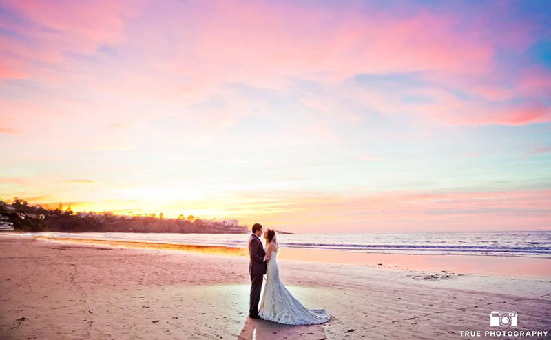 A couple posing for pictures at their beach wedding as the sun sets at La Jolla Shores beach