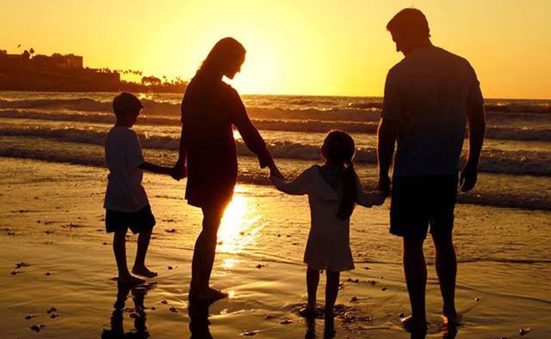 A family of four holding hands walking on La Jolla Shores beach as the sun sets