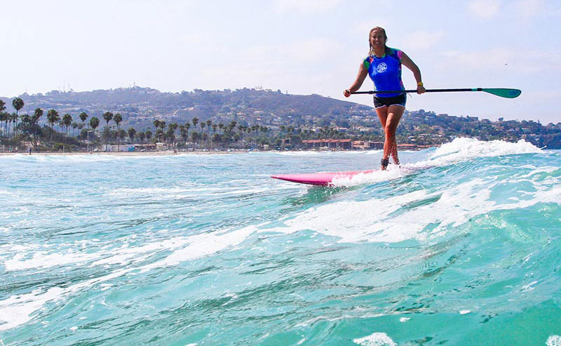 A woman stand up paddling boarding at La Jolla Shores beach