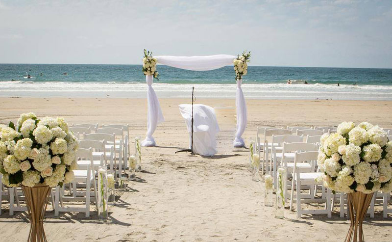 Beach wedding set up at La Jolla Shores Hotel with lush white flowers, a wedding arch made out of sheets and flowers, and complimentary seating