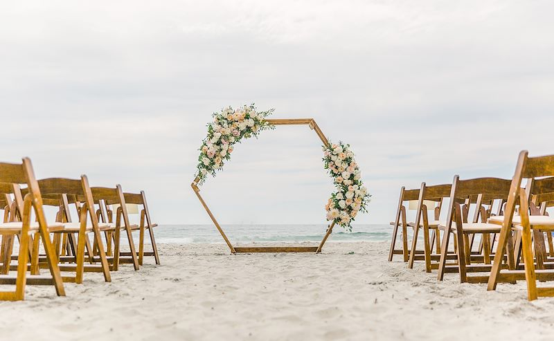 Beautiful beach wedding set up with simple and elegant arch and soft pink flowers at La Jolla Shores Hotel.