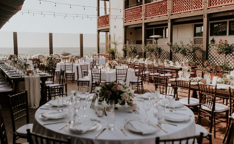 Chairs, flowers, and decorations set up in the Garden Patio for a wedding ceremony at La Jolla Shores Hotel