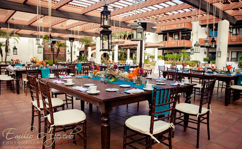 Tables, chairs, and decorations set up for a wedding reception in the Garden Patio at La Jolla Shores Hotel
